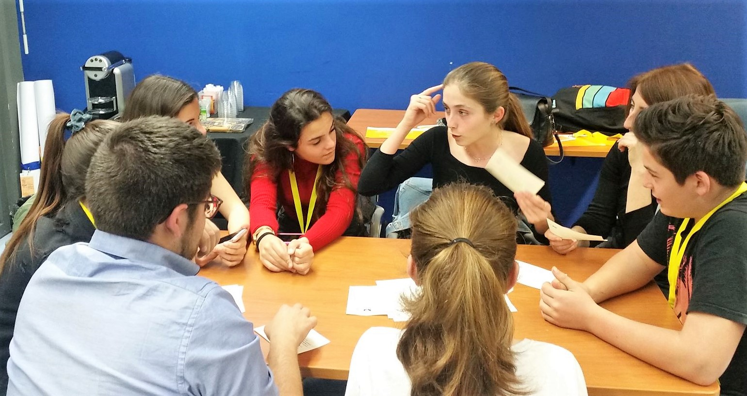students talking around a table while playing the Decide Game